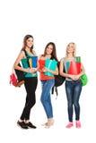 Tre lyckliga deltagare som står samman med gyckel Arkivbild