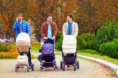 Tre lyckliga fäder på stad går parkerar in Arkivbild