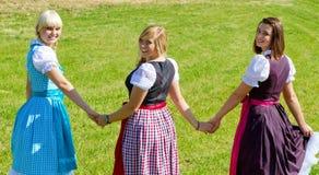 Tre lyckliga flickor i Dirndl Arkivfoton