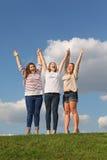 Tre lyckliga flickor poserar på gräs Arkivfoton