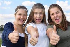 Tre lyckliga flickor skriker och tumm upp utomhus Arkivfoton