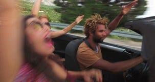Tre lyckliga hipstervänner på roadtrip i konvertibel bil stock video