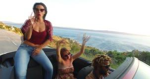 Tre lyckliga hipstervänner som har gyckel i cabriolet lager videofilmer