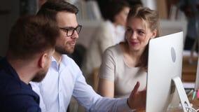 Tre lyckliga kollegor som arbetar diskutera tillsammans datorprojekt i teamwork lager videofilmer