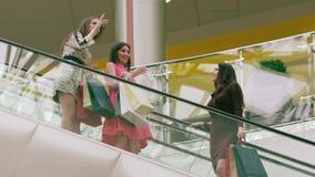 Tre lyckliga kvinnor på ner rulltrappan som tycker om deras shoppingdag lager videofilmer