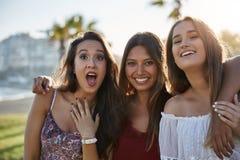 Tre lyckliga kvinnor som står dra tillsammans framsidor Arkivbilder