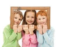 Tre lyckliga le ungar som ser bildramen Arkivfoton