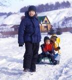 Tre lyckliga pojkar på släden royaltyfri bild