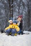 Tre lyckliga pojkar på släden royaltyfri foto
