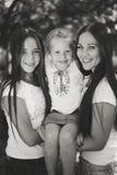 Tre lyckliga systrar som joyfully kramar och ler i sommar, parkerar Royaltyfri Fotografi
