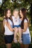 Tre lyckliga systrar som joyfully kramar och ler i sommar, parkerar Royaltyfri Bild