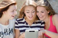 Tre lyckliga tonåriga flickavänner och minnestavladator Royaltyfri Fotografi