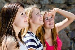 Tre lyckliga tonåriga flickavänner som tillsammans ser i en riktning Royaltyfri Fotografi