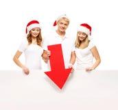 Tre lyckliga tonåringar i julhattar som pekar på ett baner Arkivbild