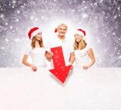 Tre lyckliga tonåringar i julhattar som pekar på ett baner Arkivbilder