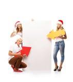 Tre lyckliga tonåringar i julhattar som pekar på ett baner Arkivfoto