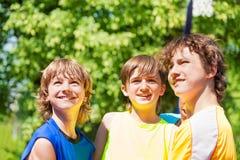 Tre lyckliga tonårs- pojkar som ler och ser upp Arkivbild