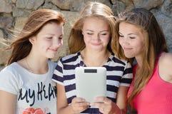 Tre lyckliga tonåriga flickavänner och minnestavladator Arkivfoto