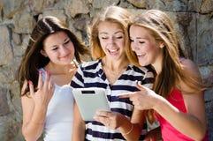 Tre lyckliga tonåriga flickavänner som ser på minnestavlaPC och skrattar på sommardag Royaltyfri Bild