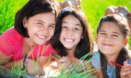 Tre lyckliga tonåriga flickor på parkerar Royaltyfri Foto