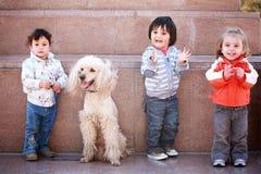 Tre lyckliga unga barn med den älsklings- hunden Arkivfoton