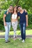 Tre lyckliga unga vänner som poserar för en stående Arkivbilder