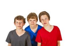 Tre lyckliga vänner klibbar tillsammans royaltyfri fotografi