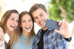 Tre lyckliga vänner som tillsammans tar selfie i gatan royaltyfri fotografi