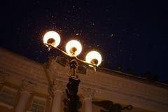 Tre lyktor skiner ljust i natten Petersburg fotografering för bildbyråer