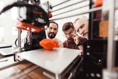 Tre män arbetar för att förbereda den utskrivavna modellen på modellen 3d av hjärtan De tillfredsställs med resultatet Royaltyfri Fotografi