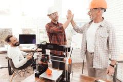 Tre män arbetar för att förbereda sig utskrivavet på en skrivare för modell 3d De står tre tillsammans runt om printerten 3d Royaltyfri Bild