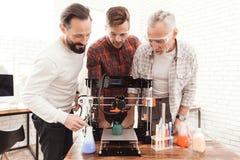 Tre män arbetar för att förbereda sig utskrivavet på en skrivare för modell 3d De står tre tillsammans runt om printerten 3d Royaltyfria Foton