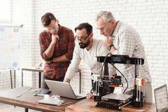 Tre män arbetar på att förbereda en skrivare 3d för utskrift Ett av dem förklarar vila av finessen trycket Arkivbilder