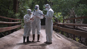 Tre män i biohazard passar anseende på en bro arkivfoton