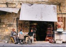 Tre män kopplar av bredvid en mattmarknad i den gamla staden av Jaffa i Tel Aviv, Israel arkivfoton