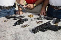Tre män med vapen på tabellen arkivbild