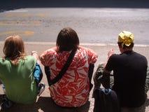Tre män sitter vid sidan av vägen Royaltyfri Bild