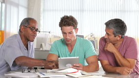 Tre män som använder minnestavladatoren i idérikt kontor arkivfilmer