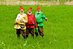 Tre män som förställas som trädgårds- gnomer Arkivbild
