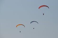 Tre män som flyger på en röd paraglider det aftonen Royaltyfri Bild