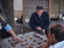 Tre män som spelar kinesiskt schack Royaltyfria Bilder