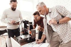 Tre män ställde in engjord skrivare 3d för att skriva ut formen De förbereder sig att lansera apparaten för första gången Royaltyfri Fotografi