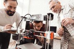 Tre män ställde in engjord skrivare 3d för att skriva ut formen De förbereder sig att lansera apparaten för första gången Arkivfoto