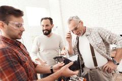 Tre män ställde in engjord skrivare 3d för att skriva ut formen De kontrollerar modellen 3d av minnestavlan Royaltyfri Foto
