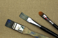 Tre målarfärgborstar på kanfas Royaltyfri Foto