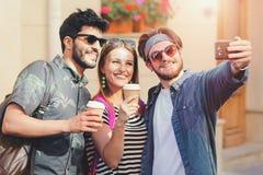 Tre mångkulturella vänner som tar selfie arkivfoto
