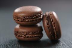 Tre macarons del cioccolato sul bordo dell'ardesia Fotografia Stock