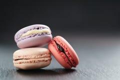 Tre macarons misti sul bordo dell'ardesia Fotografia Stock