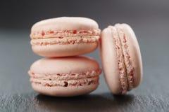 Tre macarons rosa sul bordo dell'ardesia Immagine Stock