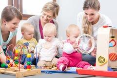 Tre madri felici che guardano i loro bambini giocare con i giocattoli multicolori sicuri immagine stock libera da diritti
